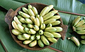 Baby bananas in a wooden bowl on banana leaf