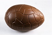 A chocolate egg on light-coloured background