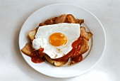 Toast with bacon, fried egg and ketchup on white plate