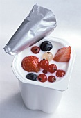 Yoghurt with various berries in opened pot