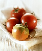 Three ripe tomatoes and one unripe one on a cloth