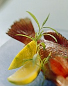 Still life with strawberry perch, lemon slices & tarragon