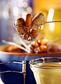 Sausage fondue, frikadeller in slotted spoon over fondue pot