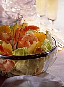 Lettuce with shrimps and oranges in glass dish