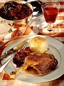 Martinmas goose with red cabbage & dumpling; glass of red wine