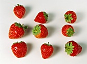 Nine strawberries arranged separately on white background
