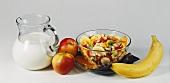 Müsli mit Früchten in Glasschale; Milchkrug, Äpfel und Banane