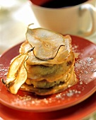 Pear pancakes with maple syrup on red plate