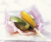 Mango on pink paper, cut into two halves, & knife