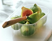 Green figs, one halved with knife in plastic punnet