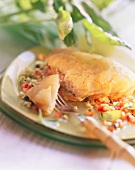 Fish fillets in potato crust on plate with fork