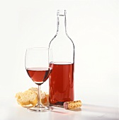 Bottle of French red wine, red wine glass, white bread, corks