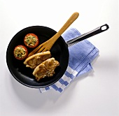 Lamb cutlets and tomatoes in non-stick frying pan