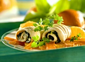 Stuffed sole rolls with spinach on carrots and oranges