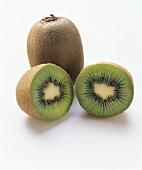 Two kiwi fruit halves in front of whole kiwi fruit