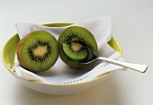 Two kiwi fruit halves with spoon on napkin in a bowl