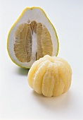 Peeled pomelo in front of halved pomelo on white background