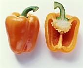 Half an orange pepper beside whole pepper