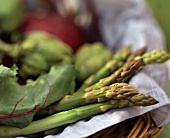 Fresh green asparagus & other vegetables in basket