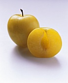 Yellow plum halves without stone; whole plum with stalk