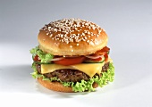 A cheeseburger with tomatoes and gherkins, light background