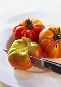 Three beefsteak tomatoes, one sliced, with knife