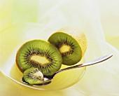 Two kiwi fruit halves & piece of kiwi fruit on spoon in a bowl