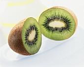 Two kiwi fruit halves on white plate