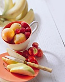 Various types of fruit & berries on plate & in cup