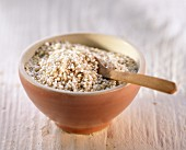 Millet in a bowl with wooden spoon