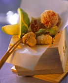 Vegetable tempura in wooden box with wedge of lime