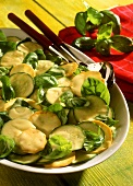 Yellow & green courgette salad with basil on white plate
