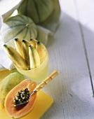 Halved papaya, bananas in bowl, musk melons behind