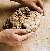 Preparing mixed-grain bread: hands forming oblong loaf