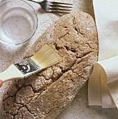 Mischbrot zubereiten: Brotlaib mit Wasser bepinseln