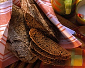 Six-grain bread with a few slices on kitchen cloth