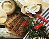 Rhenish black bread on wooden board; bread & butter; roses