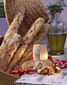 Olive baguette with cheese; décor: straw hat & olive oil