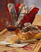 Wholemeal sticks on bread board and in basket; red wine