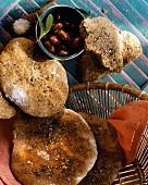 Greek mini-pitta in bread basket & beside it with olives