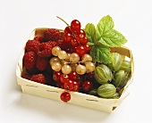 Various berries with redcurrant leaf in chip basket