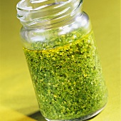 Pesto in an open jar on pale green background