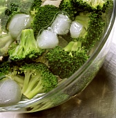 Blanched broccoli florets in dish with iced water