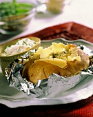 Baked potatoes in foil on plate with herb quark