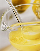 Lemon dressing in glass bowl with ladle