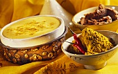 Curried cream in a bowl; curry powder and curry paste
