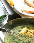 Lemon and caper butter in pan with whisk; fish fillets