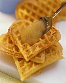 Potato waffles with apple puree on spoon above waffles