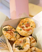 Mini-pizzas with tomatoes and herbs in a box