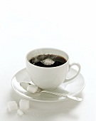 Steaming black coffee in white cup; sugar cube